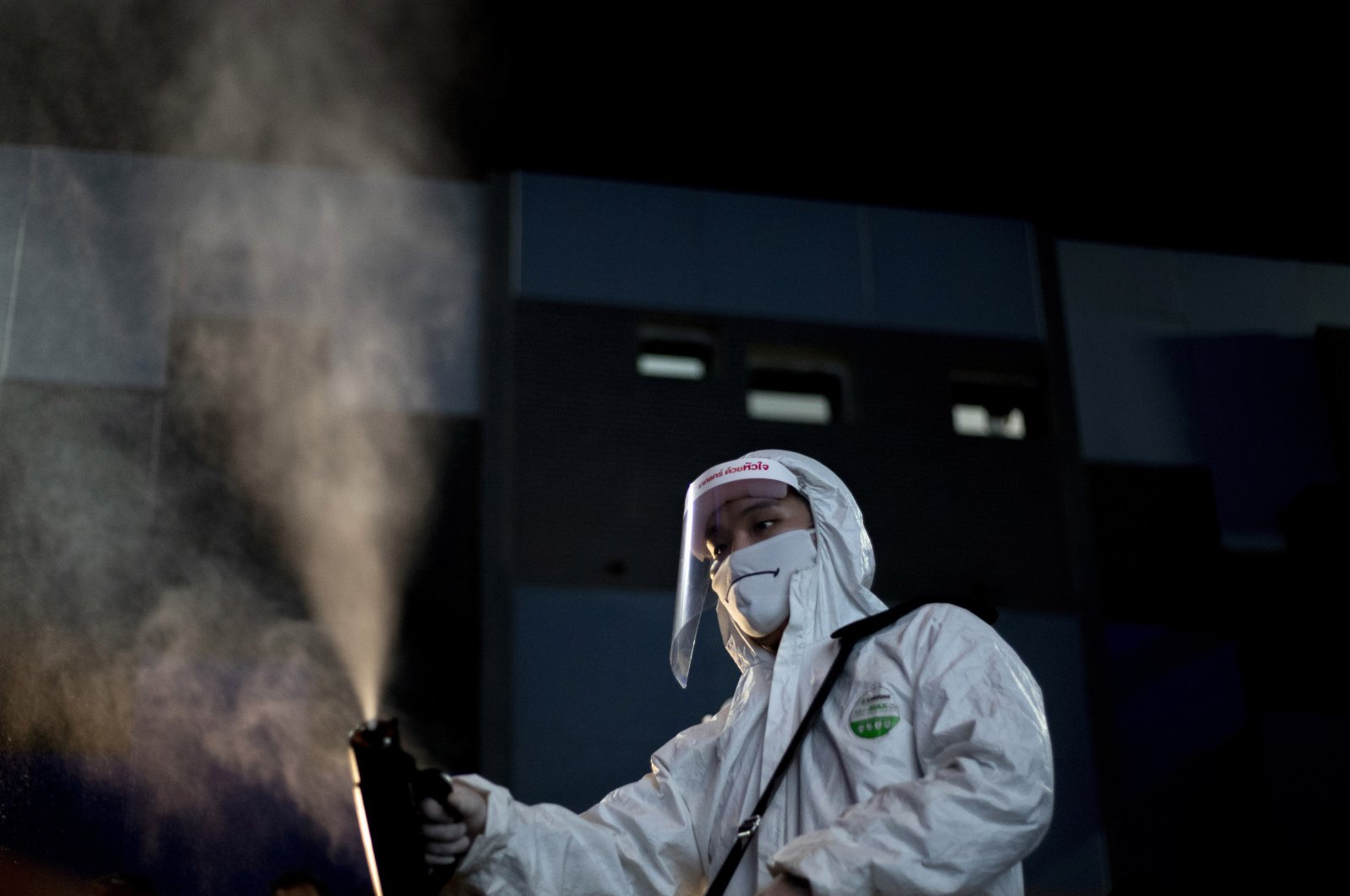 An employee sprays disinfectant as a precaution against the coronavirus at the Paragon Cineplex movie theater in Bangkok, Thailand, Monday, June 1, 2020. (AP Photo)