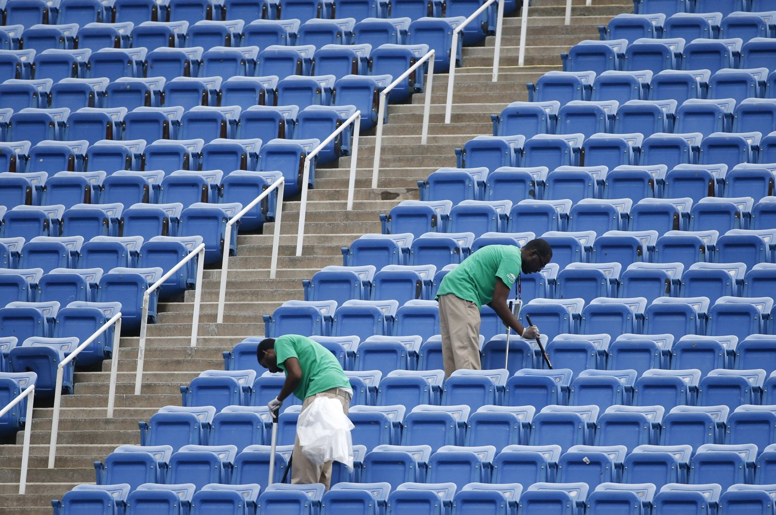 Workers clean the empty stands in Arthur Ashe Stadium after the women's semifinal matches were postponed because of rain at the U.S. Open tennis tournament in New York, U.S., Sept. 10, 2015. (AP Photo)