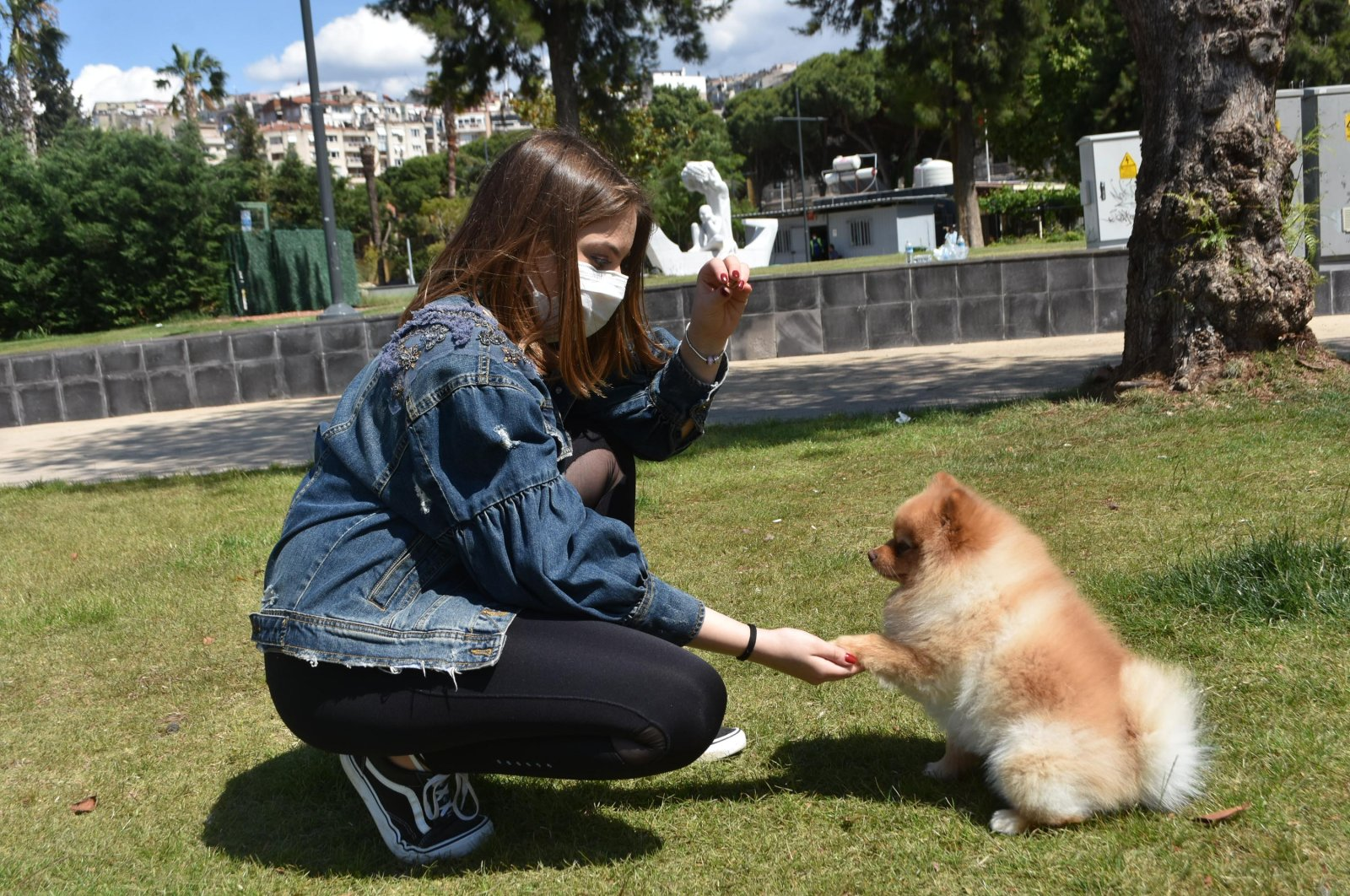 A woman plays with her dog in a park, Izmir, June 1, 2020. (DHA Photo)