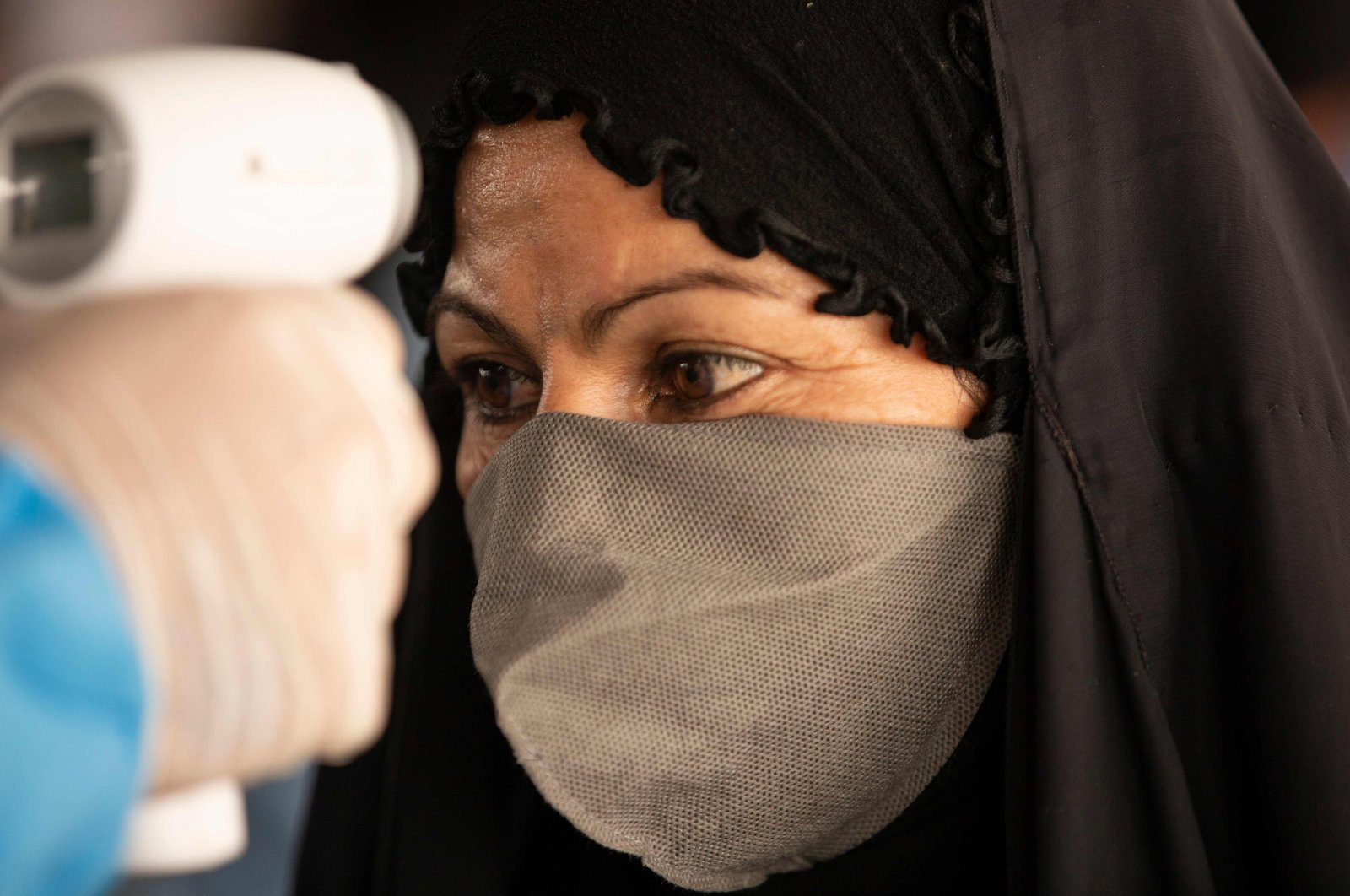An Iraqi woman who had been stranded in Iran due to the coronavirus pandemic, gets her temperature checked by a health worker upon her arrival to Iraq via the Al-Shalamija border crossing, west of the southern city of Basra, Iraq, May 27, 2020. (AFP Photo)