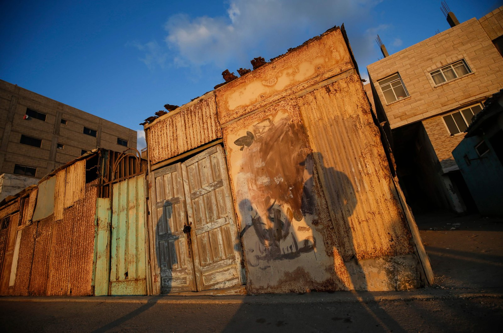Palestinian men cast their shadows on a bangalow, as they gather at sunset in Gaza City, May 28, 2020. (AFP Photo)