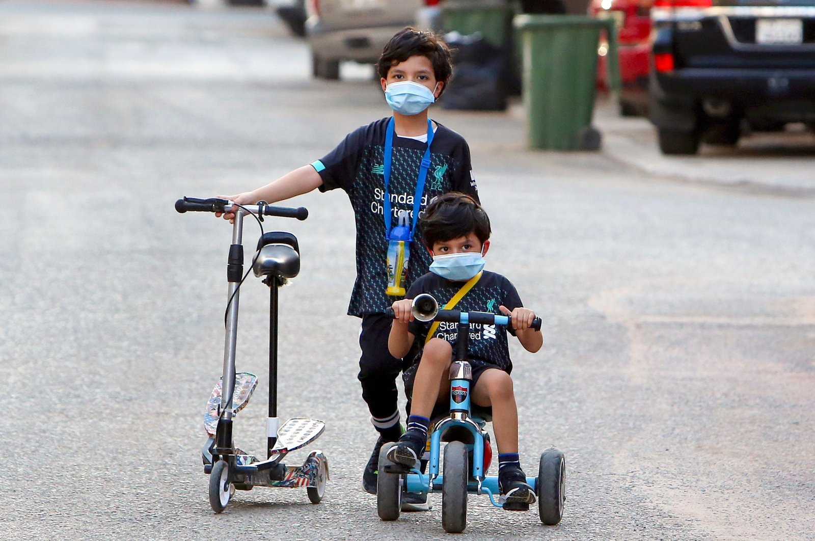 Kuwaiti children, wearing protective facemasks, cycle in a street in the Salwa district of Kuwait City, May 29, 2020. (AFP Photo)