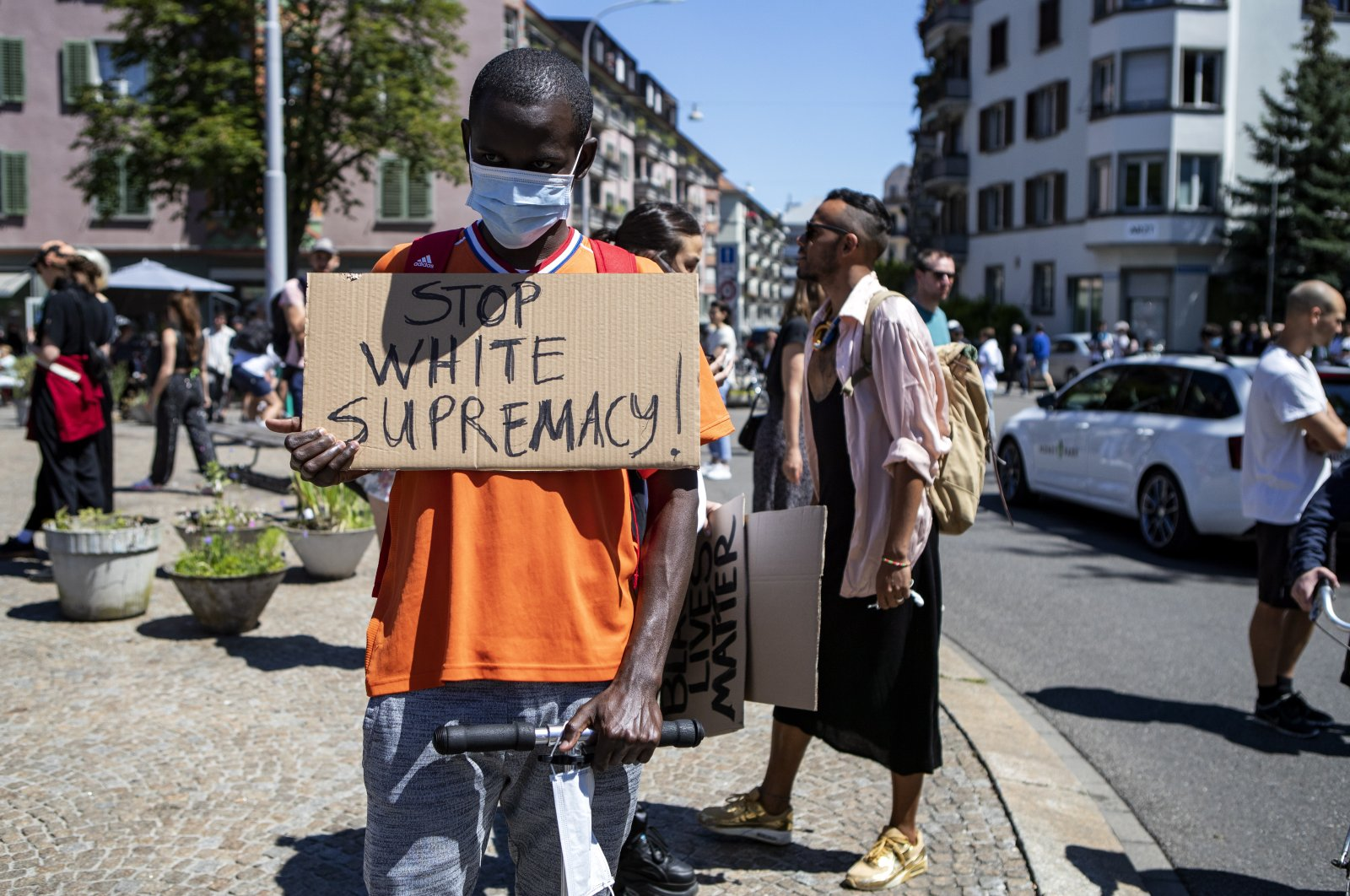 """An activist wearing a face mask holds up a placard reading in English, """"Stop White Supremacy!"""" as he takes part in a Black Lives Matter protest against the recent death of George Floyd, in Zurich, Switzerland, June 1, 2020. (EPA Photo)"""