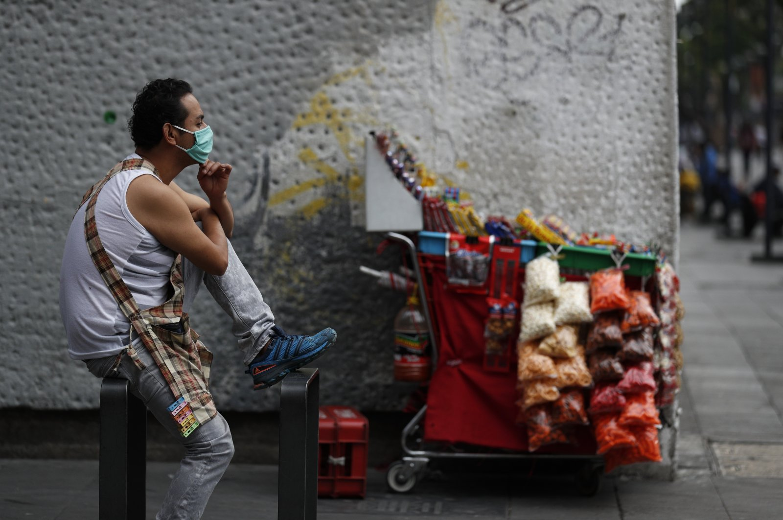 A snack vendor wears a mask as he waits for customers by his cart, in central Mexico City, Mexico, May 31, 2020. (AP Photo)