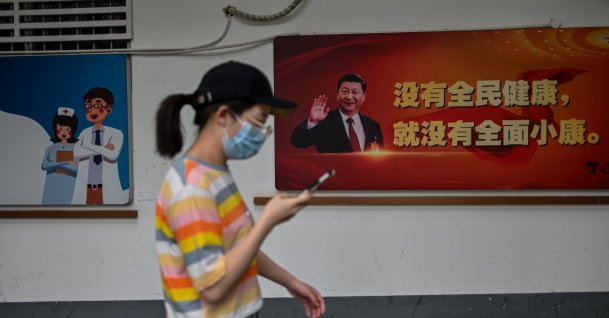 A woman walks past a photograph of China's President Xi Jinping displayed outside a hospital, Wuhan, May 28, 2020. (AFP Photo)