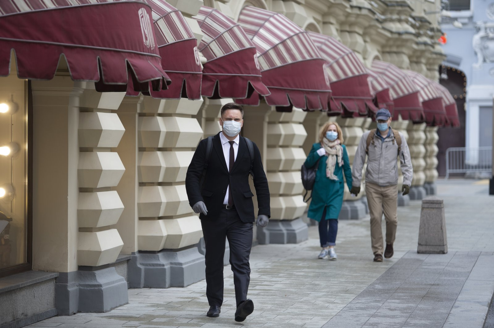 People wearing face masks and gloves walk to the entrance of GUM, also known as the State Department Store, after it reopened in Moscow, Russia, June 1, 2020. (AP Photo)