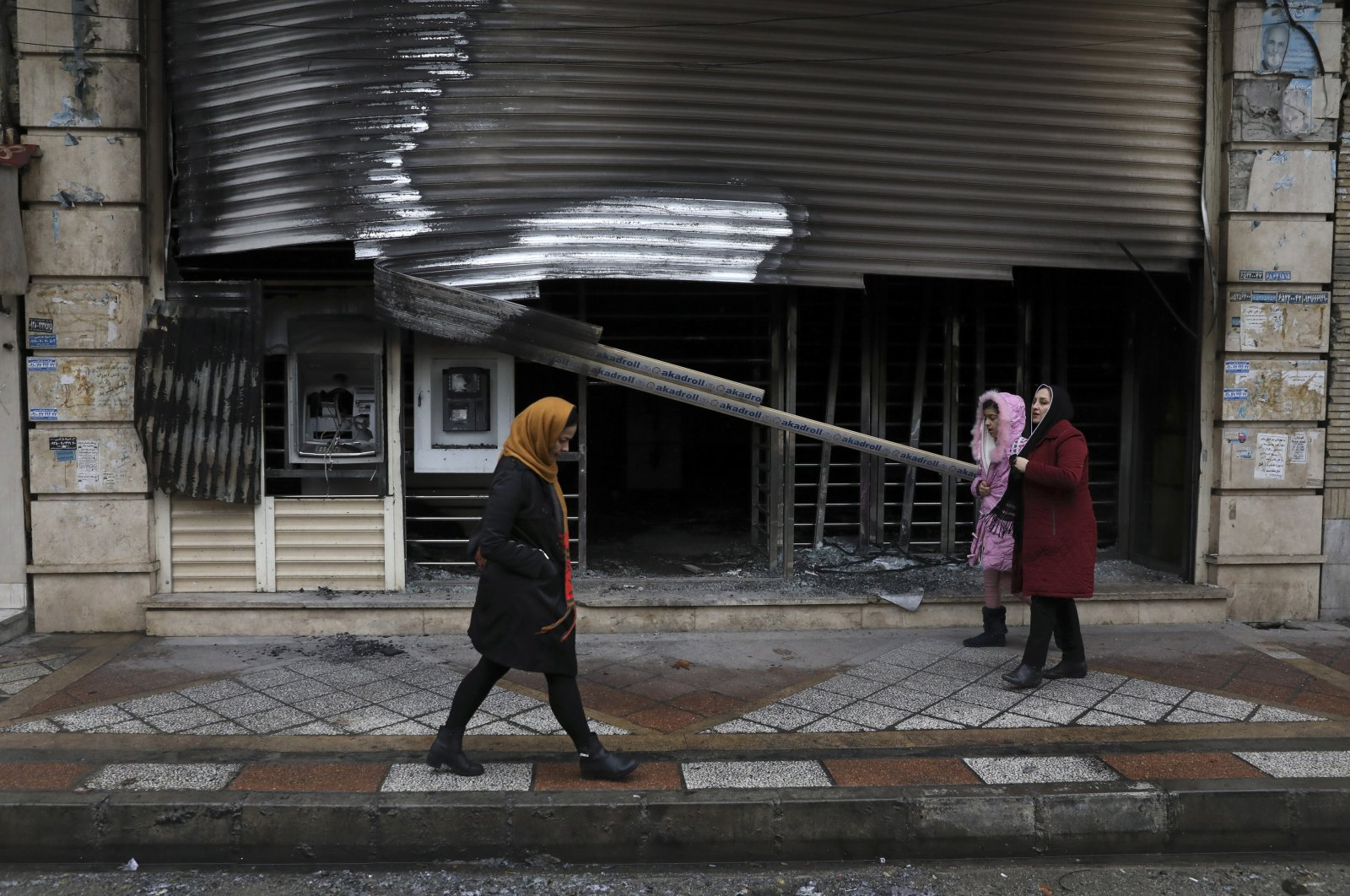 People walk past a bank that was burned during protests over government-set gasoline prices, Shahriar, Iran, Nov. 20, 2019. (AP Photo)