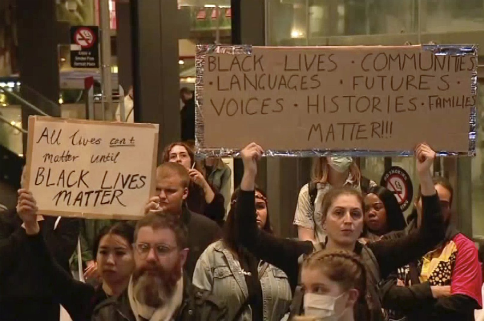 """Protesters hold up placards reading """"Black Lives Matter"""" during a peaceful rally in Perth, Australia, Monday, June 1, 2020. (Channel 10 via AP)"""