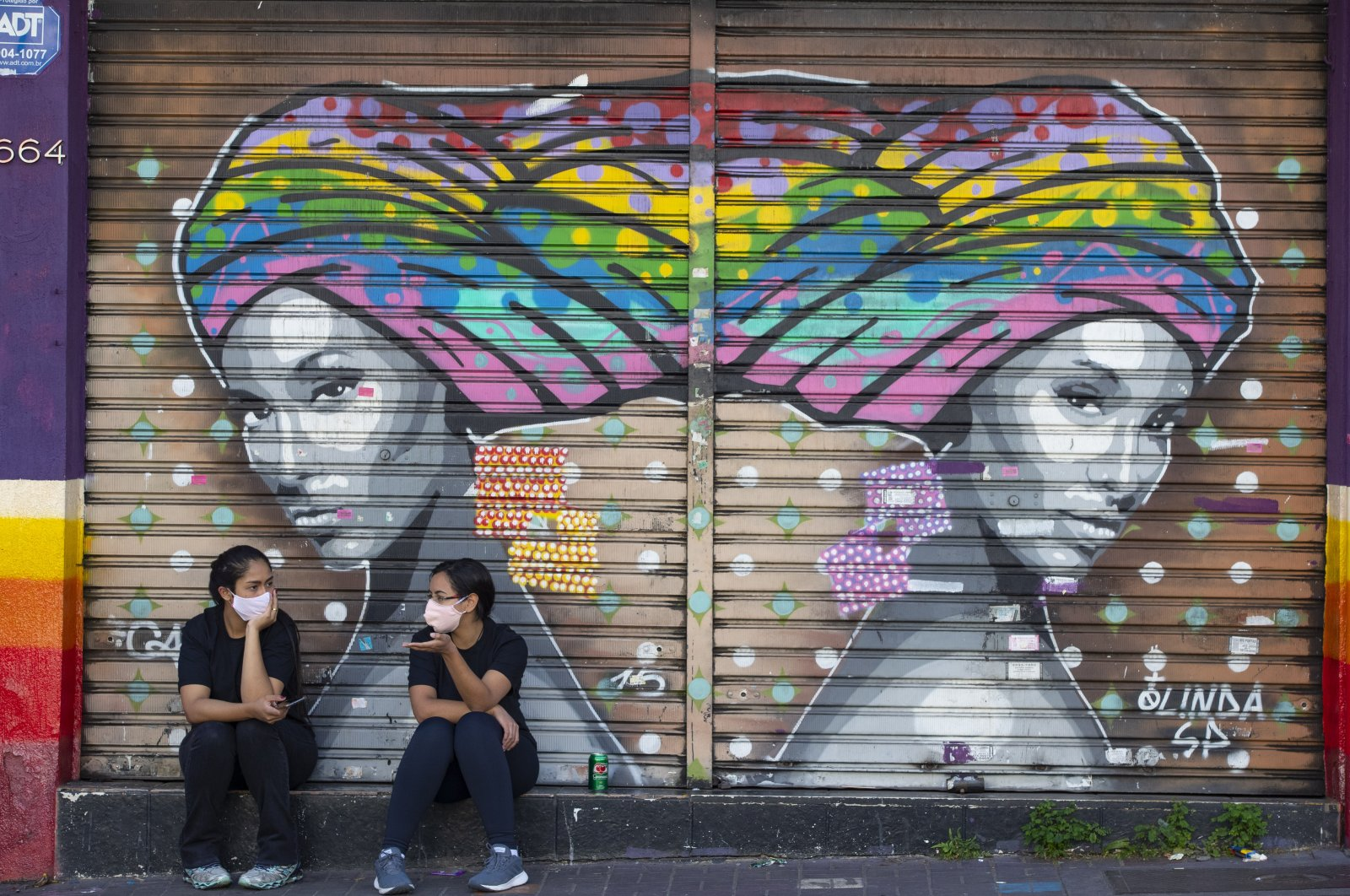 Women talk outside a closed outfit store during a quarantine, Sao Paulo, June 1, 2020. (AP Photo)
