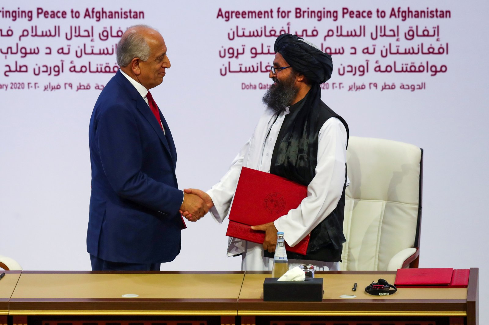 Mullah Abdul Ghani Baradar, the leader of the Taliban delegation, and Zalmay Khalilzad, U.S. envoy for peace in Afghanistan, shake hands after signing an agreement at a ceremony between members of Afghanistan's Taliban and the U.S., Doha, Feb. 29, 2020. (REUTERS Photo)