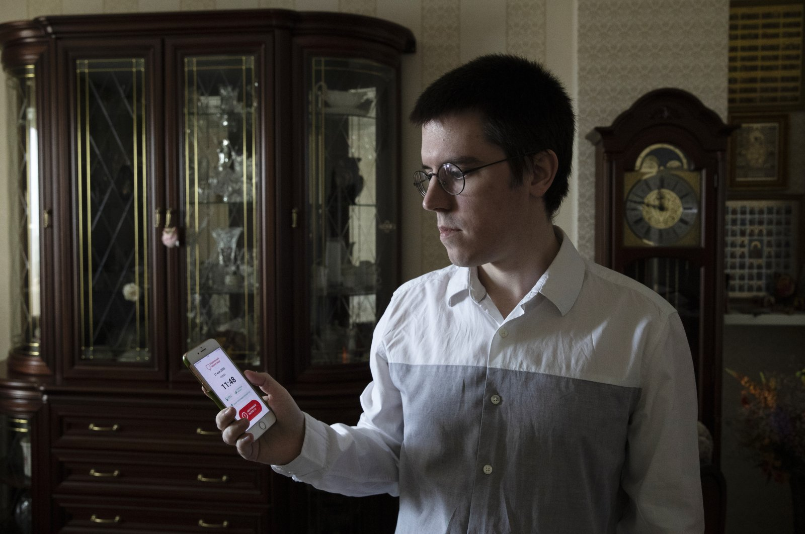 Vladimir Perevalov shows a Social Monitoring app installed on his phone in his apartment in Shcherbinka, outside Moscow, Russia, May 27, 2020. (AP Photo)
