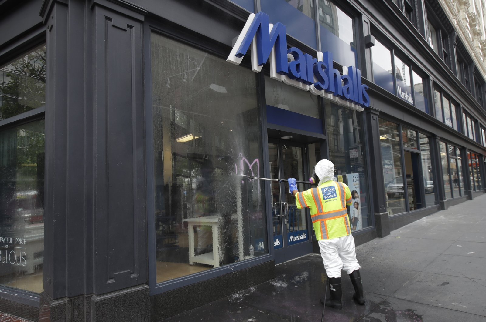 A worker with San Francisco Public Works sprays graffitti off the window of a Marshalls store in San Francisco, California, U.S., May 31, 2020, after protests over the Memorial Day death of George Floyd. (AP Photo)