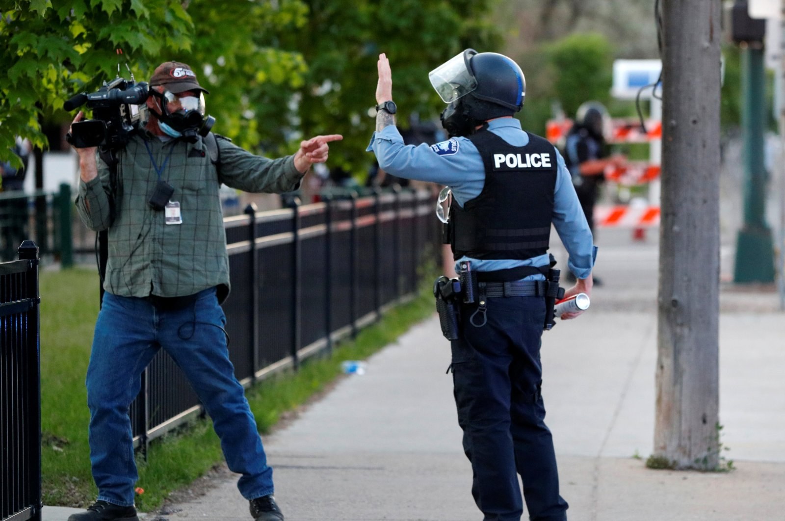 A Minneapolis police officer tells a TV cameraman to clear the area, Minneapolis, Minnesota, U.S., May 30, 2020. (REUTERS Photo)