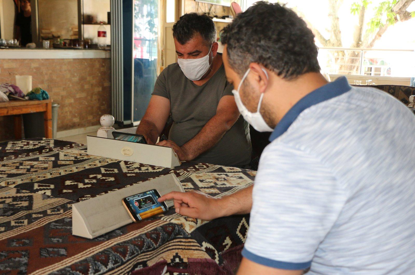 Customers play okey on their cellphones in Adıyaman, Turkey, June 2, 2020. (DHA Photo)