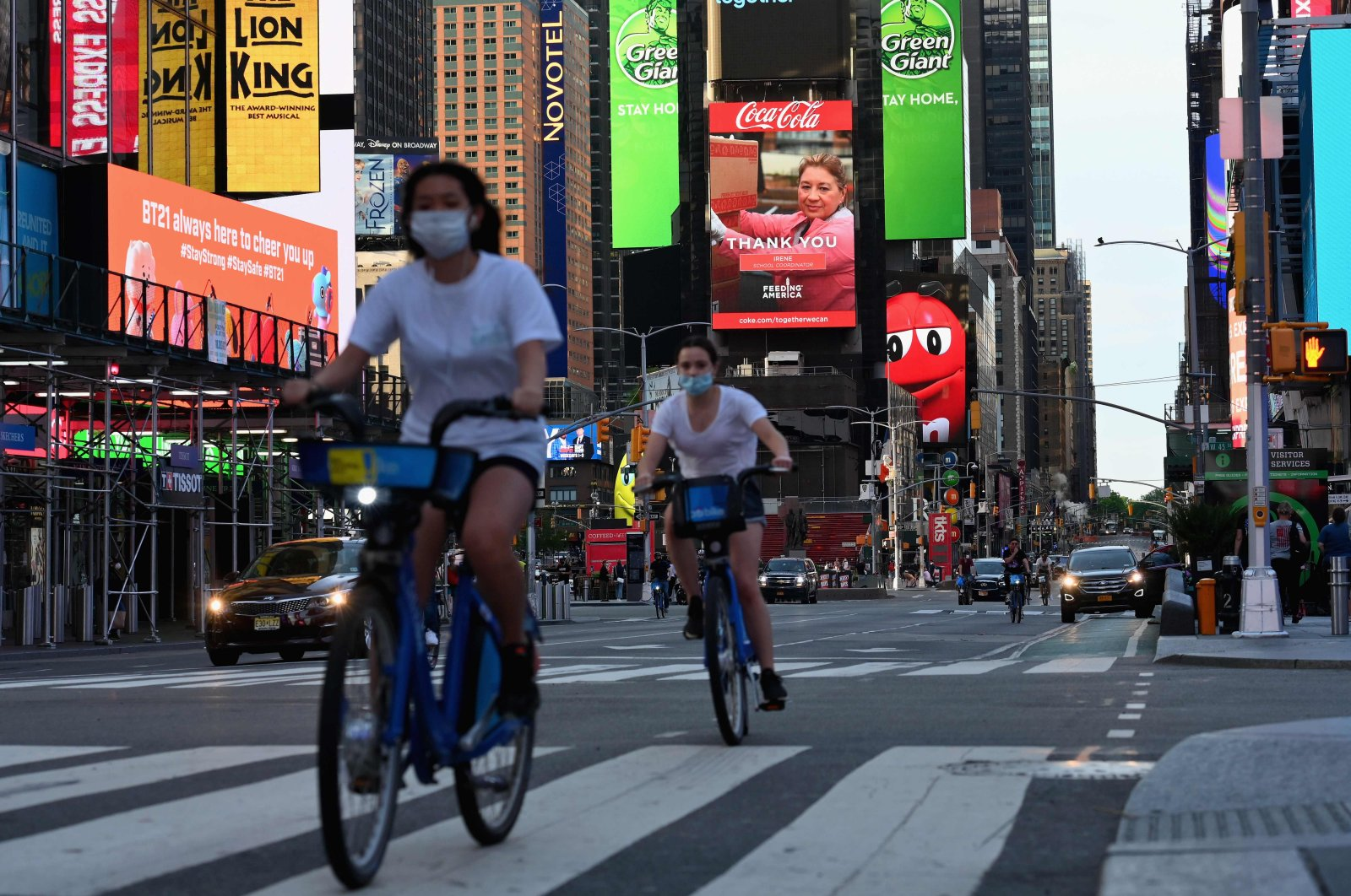 People wearing face masks ride their bikes through Times Square in New York City, amid the novel coronavirus pandemic, May 27, 2020. (AFP Photo)