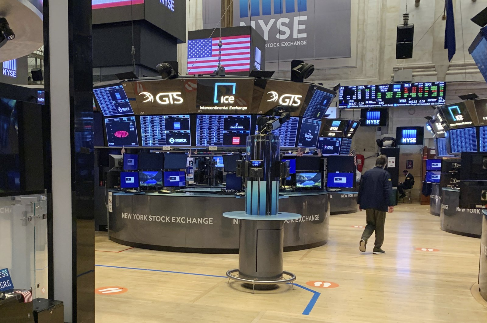 A trader walks across the partially reopened trading floor of the New York Stock Exchange, Thursday, May 28, 2020. Stocks are pushing higher in morning trading on Wall Street Thursday, extending this week's rally built on hopes for a coming economic revival. (AP Photo)