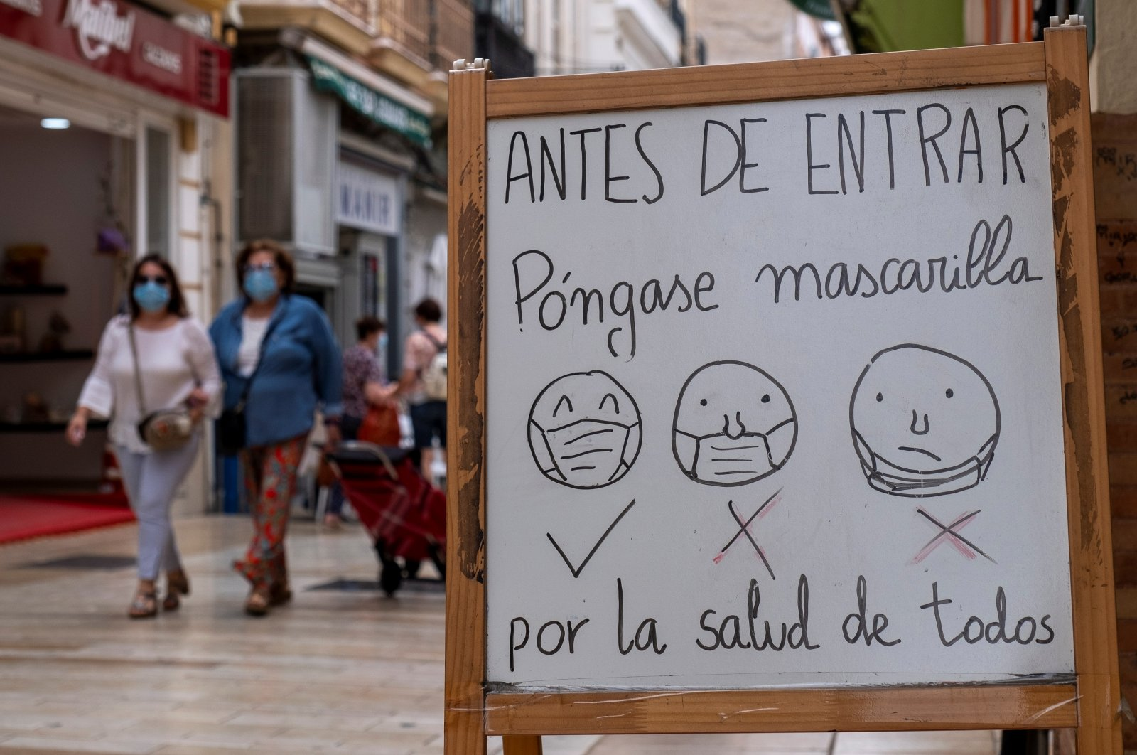 A white board explains with drawings how to wear facial masks correctly at the entrance to a shop, Huelva, Spain, June 1, 2020. (EPA Photo)