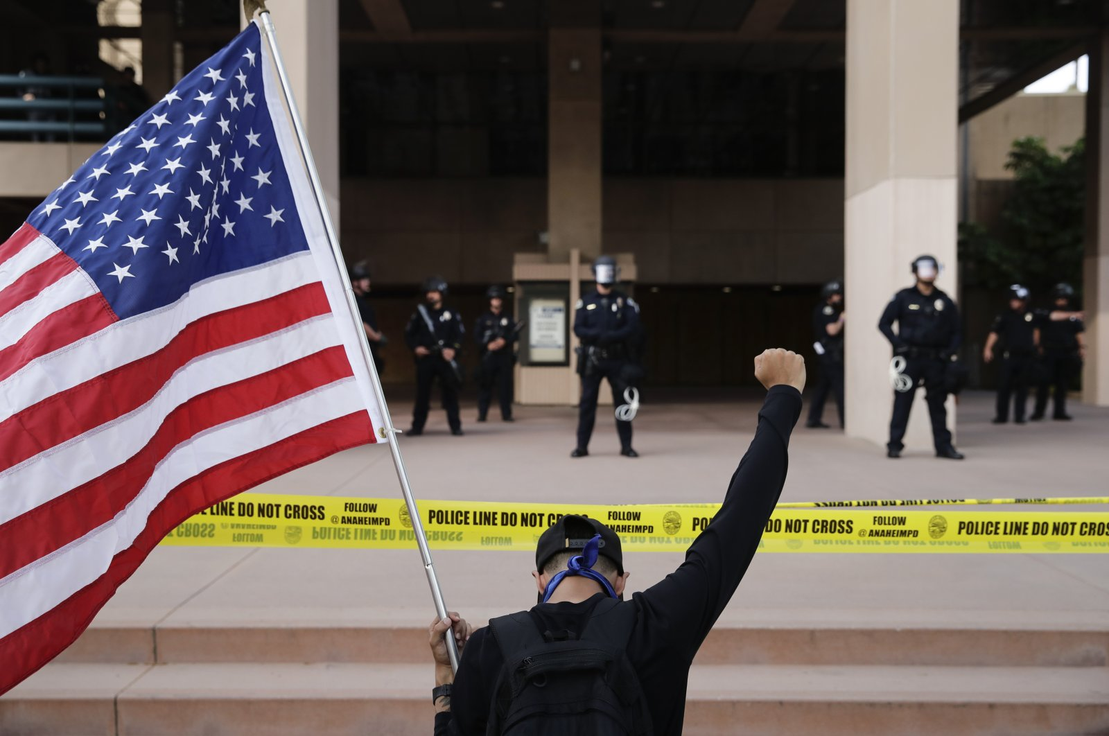 A demonstrator holds up his fist while kneeling before police officers during a protest over the death of George Floyd, Anaheim, Calif., June 1, 2020. (AP Photo)