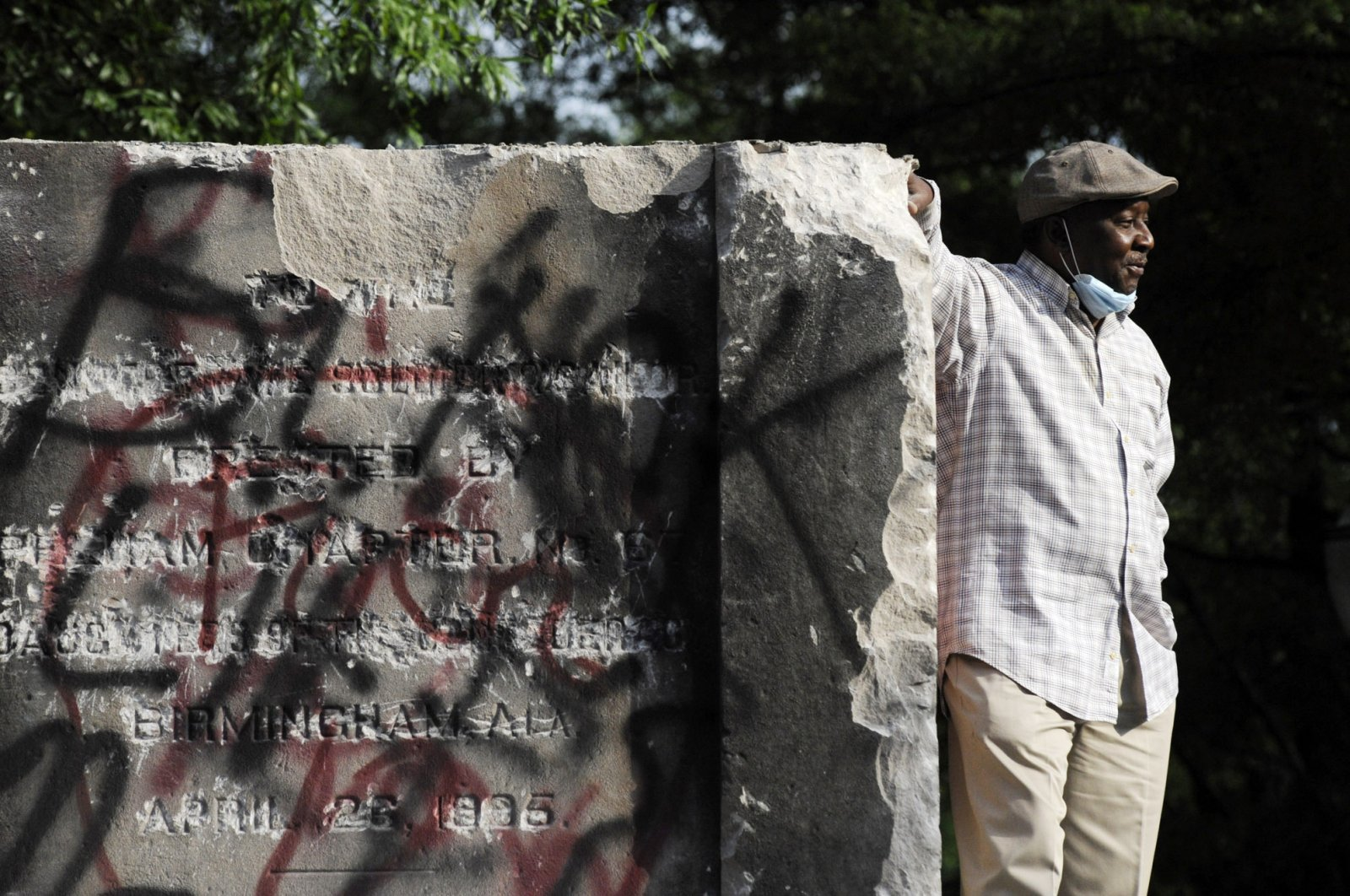 Robert Walker poses for a photograph on the remains of a Confederate memorial that was removed overnight in Birmingham, Ala., Tuesday, June 2, 2020. (AP Photo)