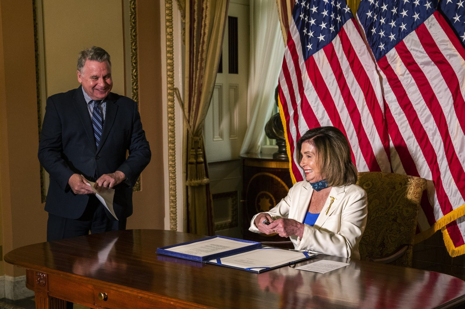 House Speaker Nancy Pelosi of Calif., talks to Rep. Chris Smith, R-N.J. (L) after signing the Uighur Human Rights Policy Act at the Capitol in Washington, June 2, 2020. (AP Photo)