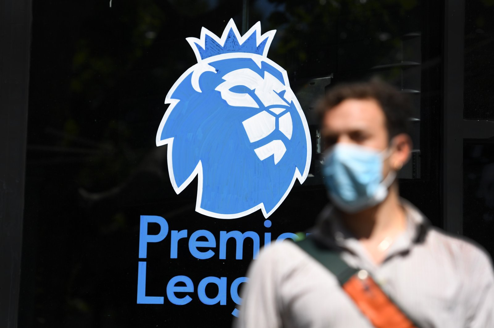 A man wearing a protective mask walks past the English Premier League logo in London, May 29, 2020. (EPA Photo)