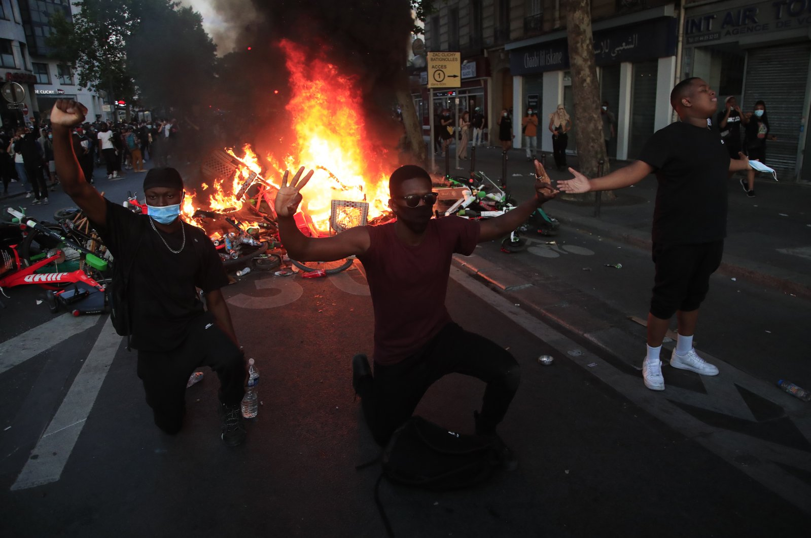 Protesters kneel and react by a burning barricade during a demonstration in Paris, June 2, 2020. (AP Photo)