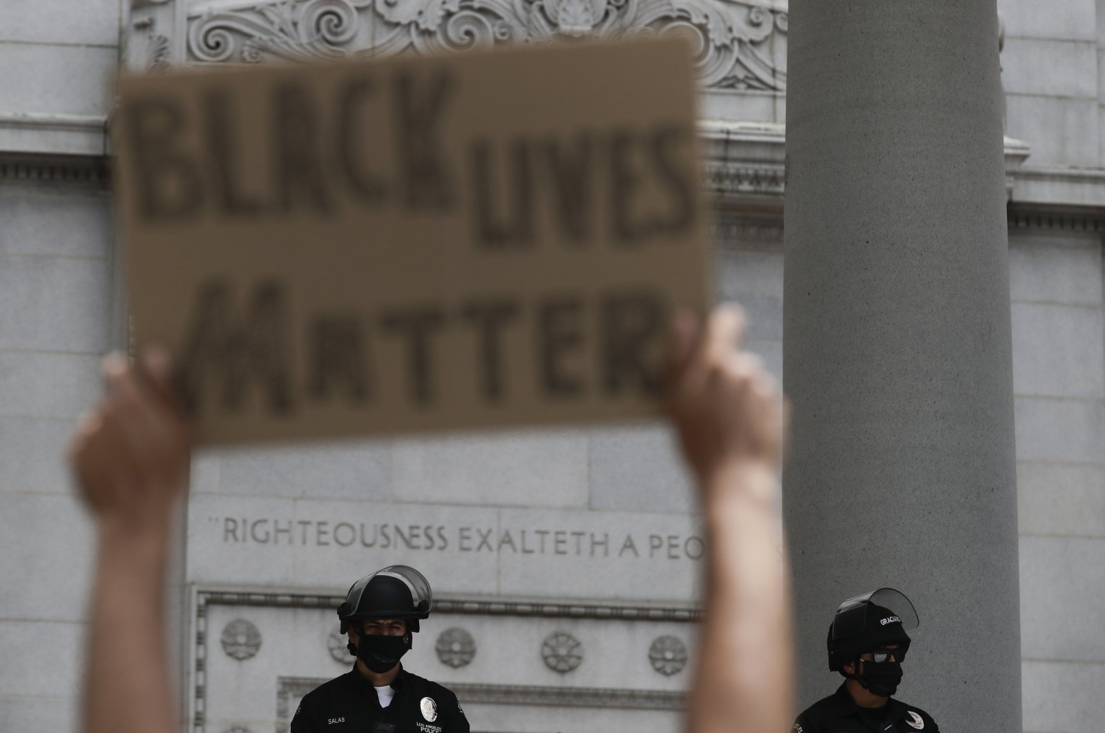 A man holds up a sign in front of police officers during a protest, in Los Angeles, California, June 2, 2020. (AP Photo)