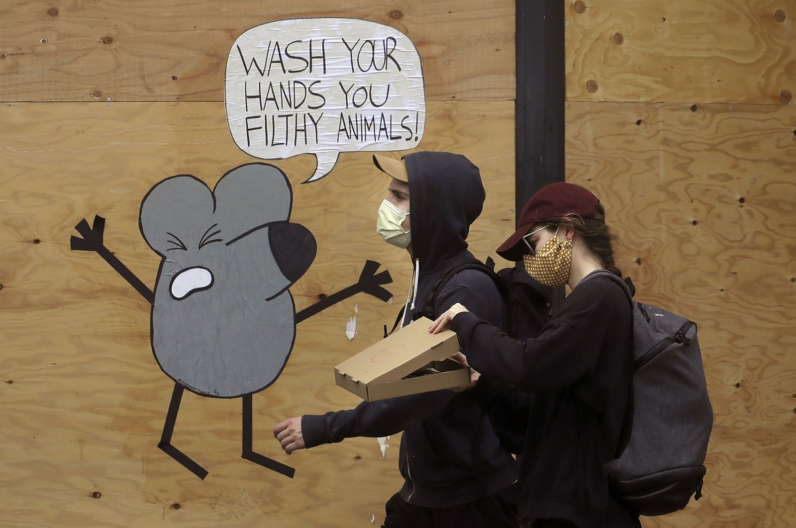 A man and woman wearing masks to prevent the spread of the coronavirus walk past a cartoon advising people to wash their hands on a boarded-up storefront in San Francisco, California, U.S., May 2, 2020. (AP Photo)
