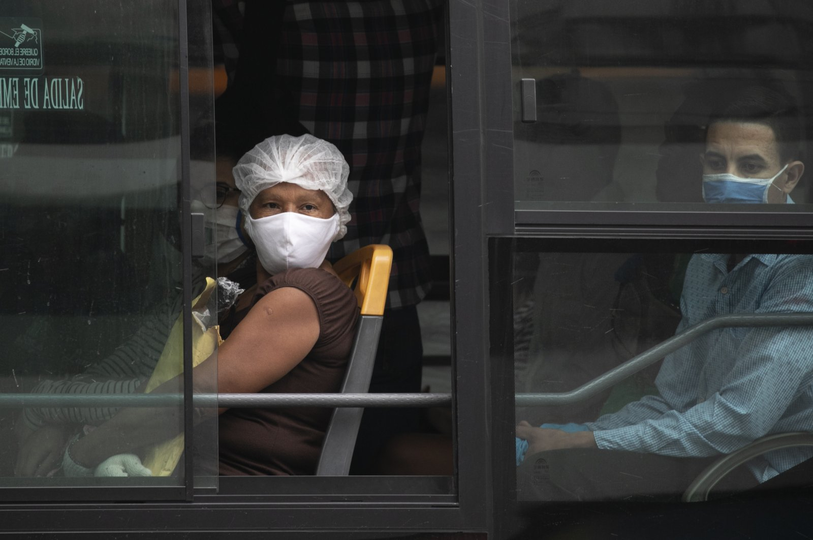 Commuters wearing face masks due to the new coronavirus pandemic ride buses in Caracas, Venezuela, June 1, 2020. (AP Photo)
