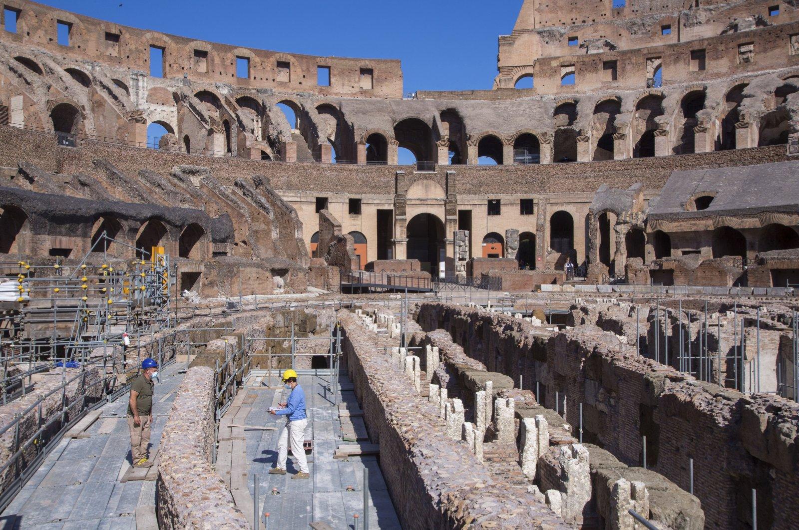 Restorers work inside the Colosseum in Rome, June 1, 2020. (AP Photo)