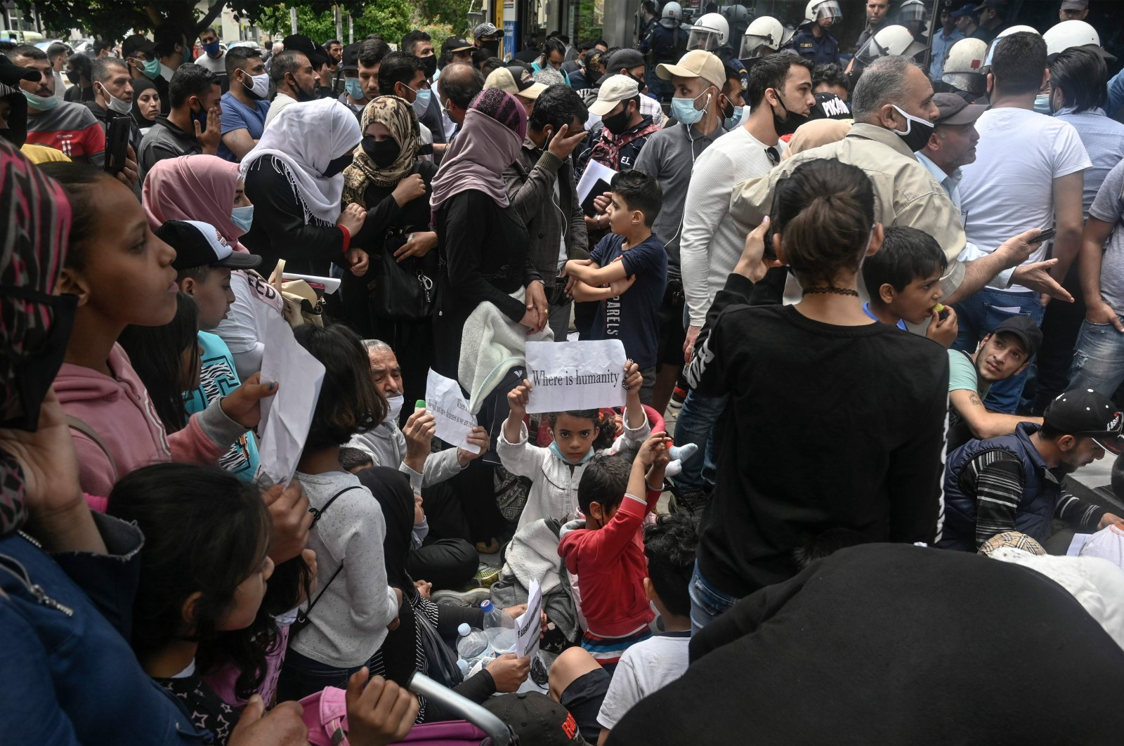 Refugee families holding their asylum documents and a child holding a placard reading 'where is humanity' protest outside the UNHCR offices in Athens, May 29, 2020. (AFP)
