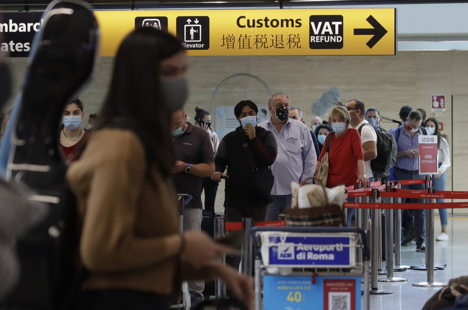 People wait in line at the check-in for a flight to Dusseldorf, Germany, at Rome's Fiumicino airport, June 3, 2020. (AP Photo)
