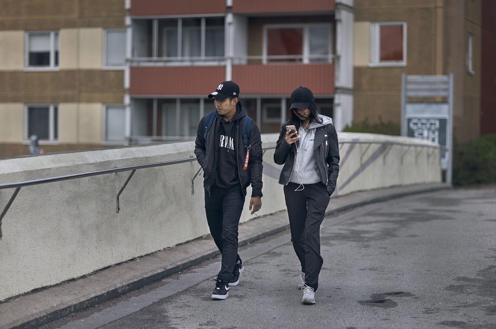 A young couple walks along a bridge in Rinkeby-Kista borough in Stockholm, Sweden, April 28, 2020. (AP Photo)