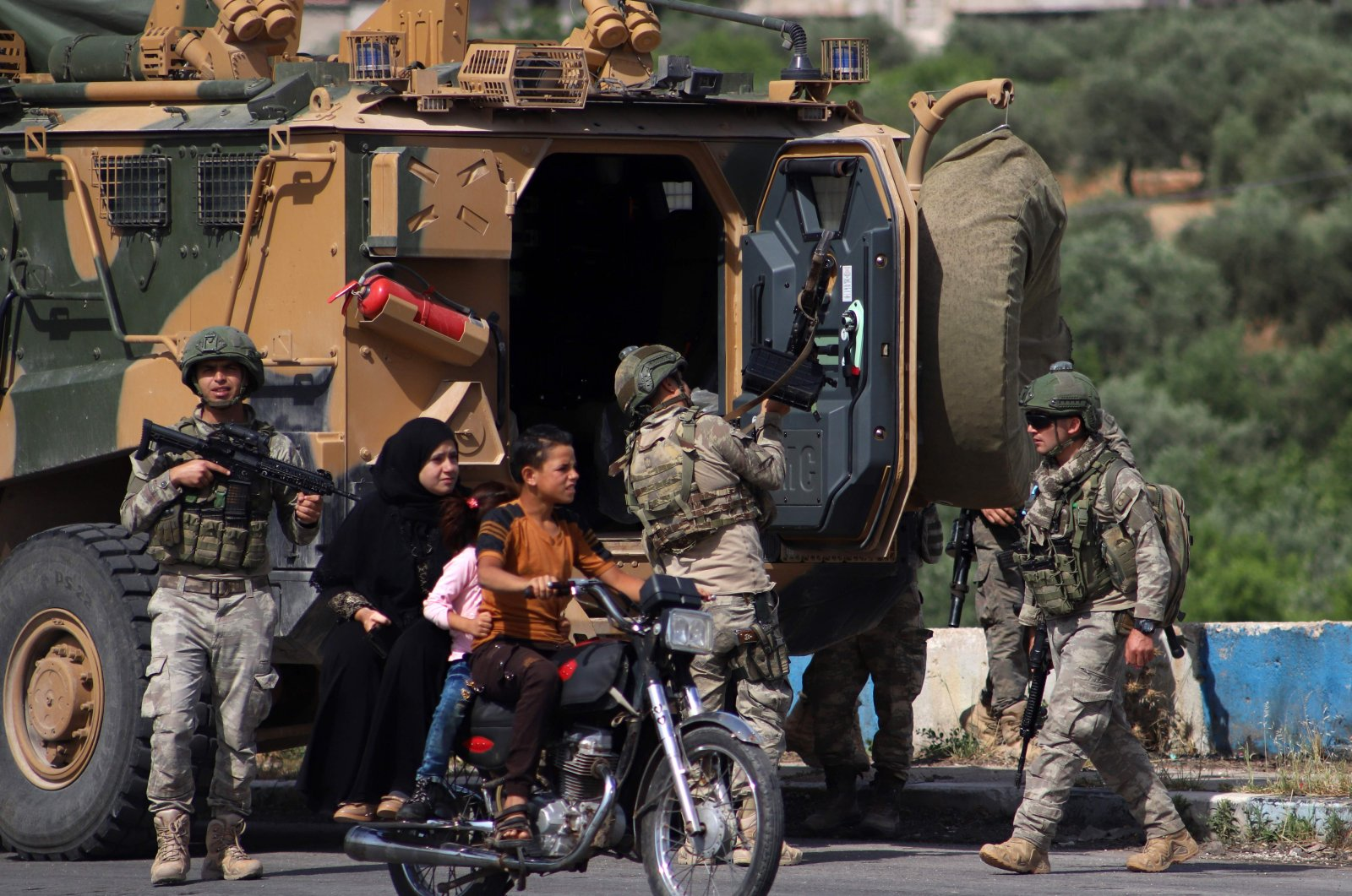 A youth rides a motorcycle carrying a woman and children past a Turkish armoured vehicle part of a joint Turkish-Russian military patrol along the M4 highway in Ariha in the opposition-held northwestern Syrian province of Idlib, June 2, 2020. (AFP Photo)