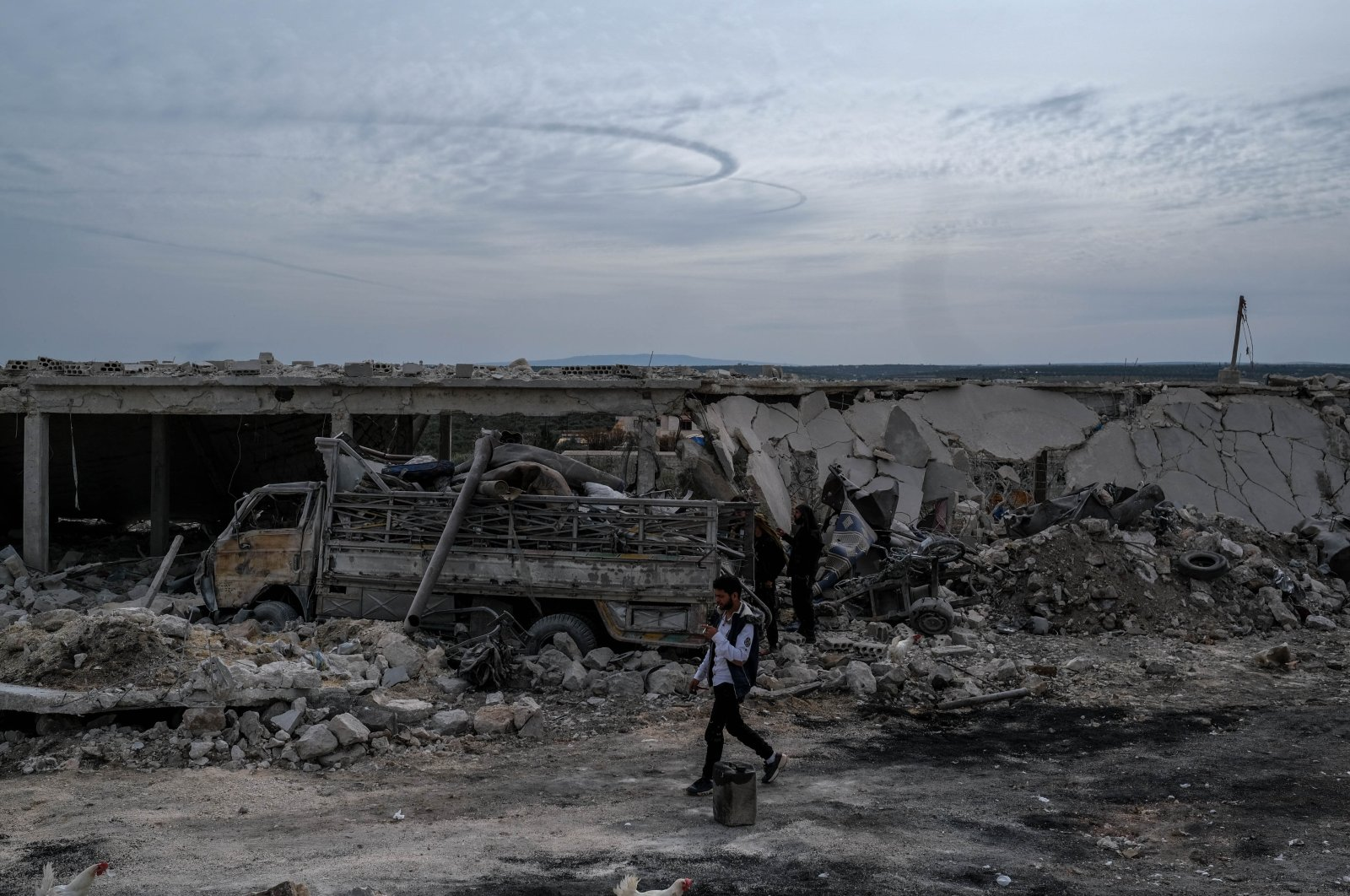 A Syrian man walks in between the ruins of buildings hit by Syrian regime and Russian attacks, March 11, 2020.