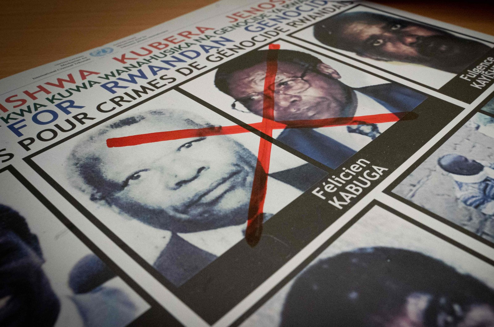 A photo shows a red cross drawn on the face of Felicien Kabuga, one of the last key suspects in the 1994 Rwandan genocide, on a wanted poster at the Genocide Fugitive Tracking Unit office in Kigali, Rwanda, May 19, 2020. (AFP Photo)