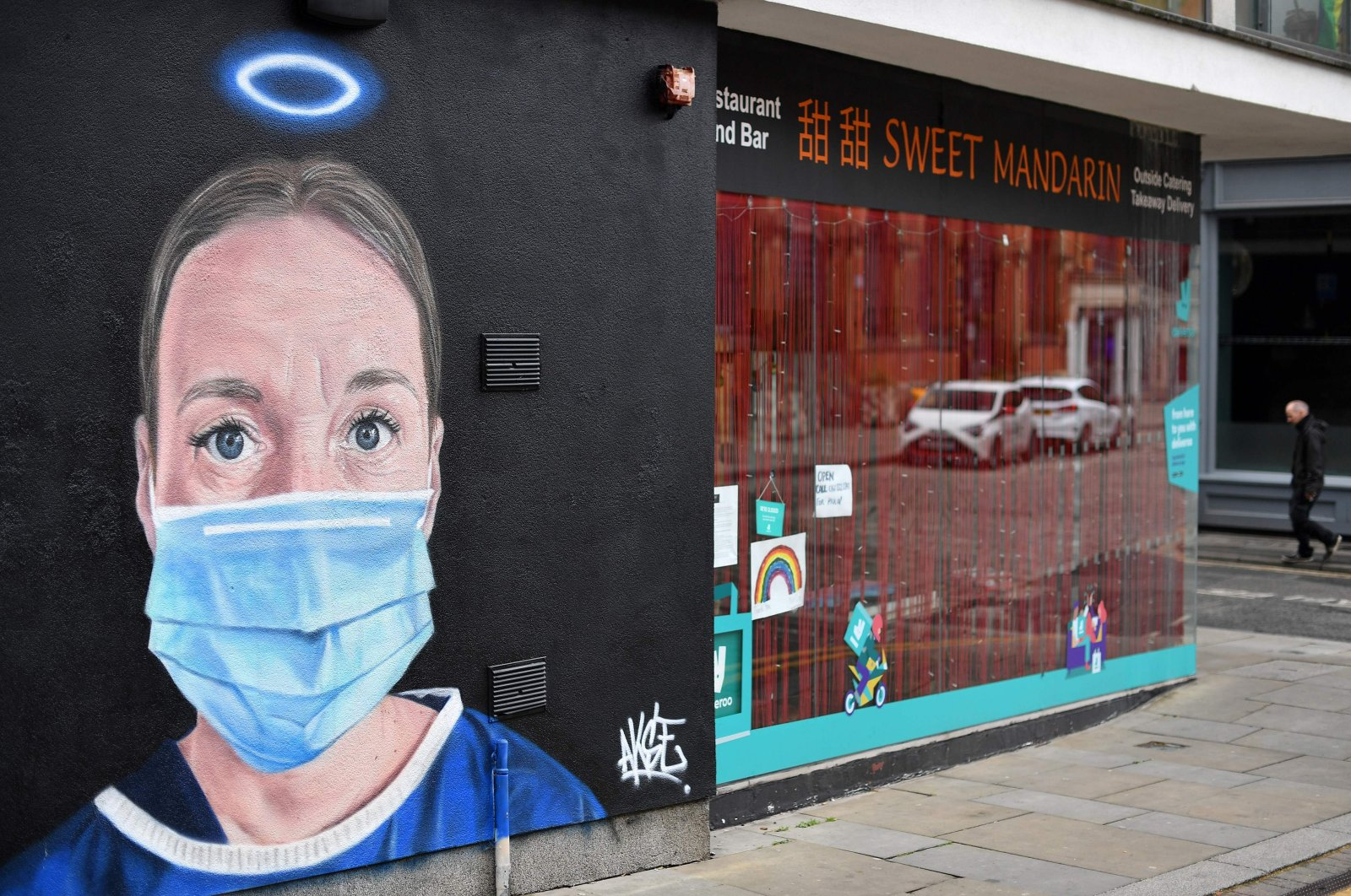 A pedestrian walks past street art graffiti, depicting a nurse with an angel's halo above her head, Manchester, June 3, 2020. (AFP Photo)