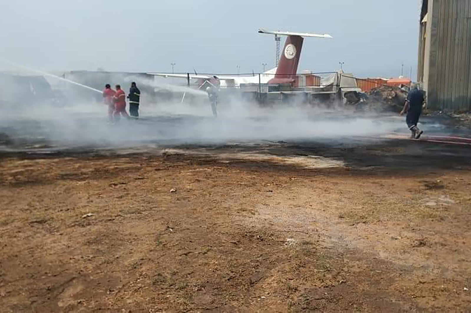 A handout picture released by the media office of Libya's UN-recognised Government of National Accord (GNA) on May 9, 2020 shows firefighters extinguishing a fire following an attack on the Mitiga airport in the capital Tripoli. (AFP Photo)