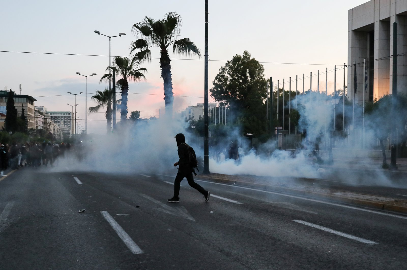 A protester outside the U.S. embassy in Athens walks next to tear gas, Athens, June 3, 2020. (REUTERS Photo)