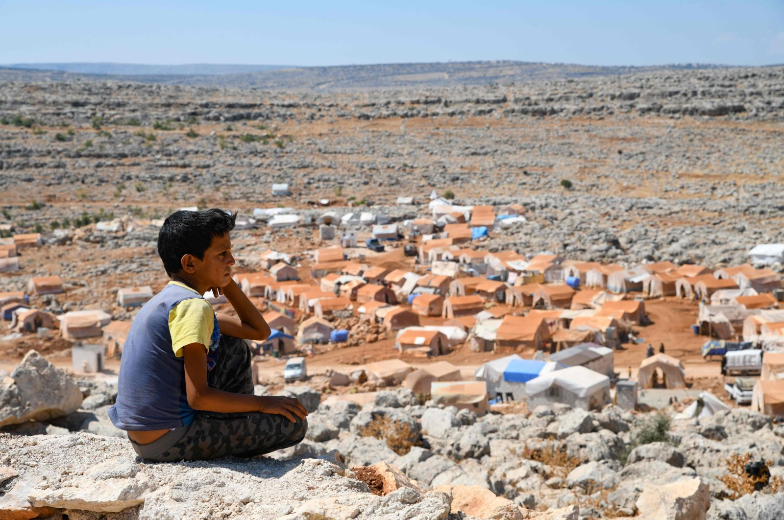 A young Syrian boy who was displaced from the town of Khan Sheikhoun gazes from a small hilltop at the makeshift camp where he currently lives, in the northern countryside of Idlib province near the Turkish border, Sept. 8, 2019. (AFP Photo)