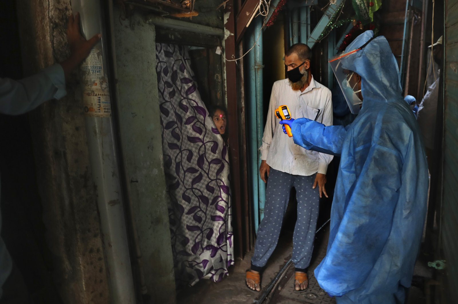 A doctor checks the temperature of a girl in Dharavi, one of Asia's largest slums, during lockdown to prevent the spread of the new coronavirus in Mumbai, India, April 13, 2020. (AP Photo)