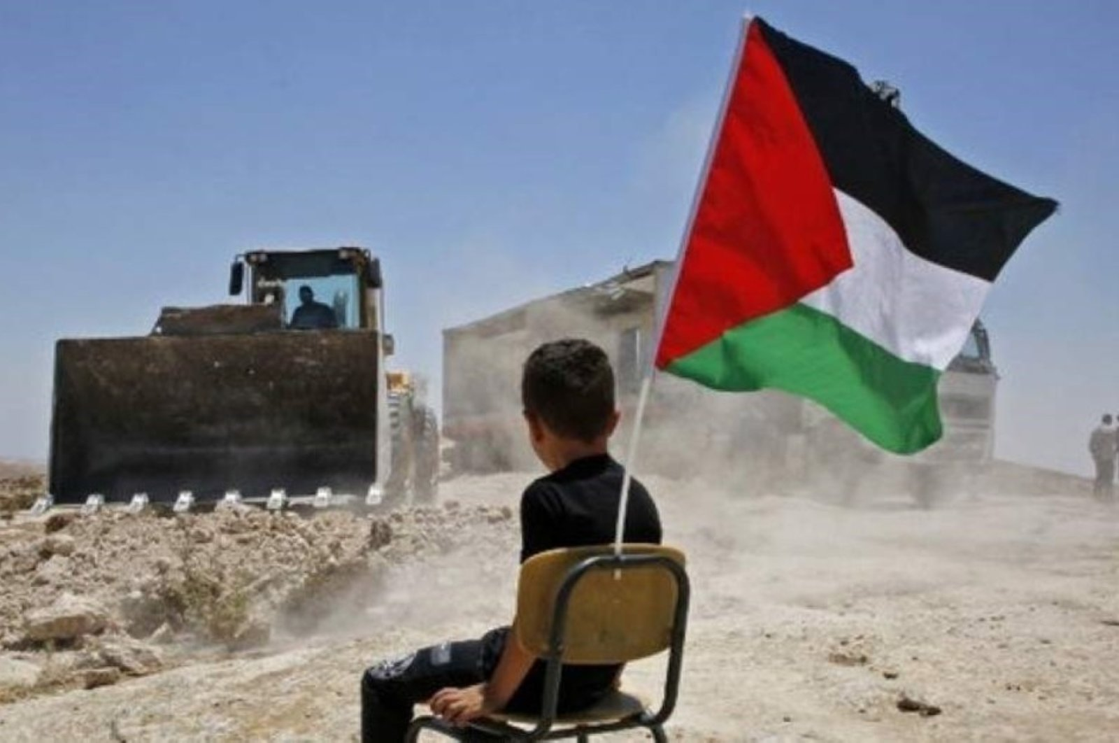 A Palestinian boy sits on a chair with a national flag as Israeli authorities demolish a school site in the village of Yatta, occupied West Bank, July 11, 2018. (AFP Photo)