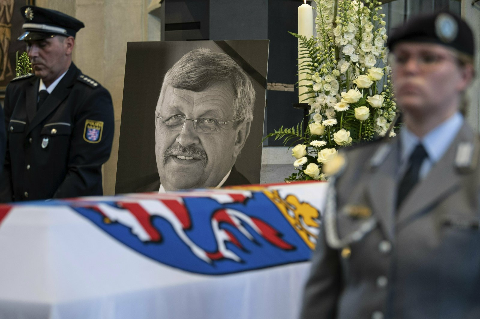 In this file photo a picture of Walter Luebcke stands behind his coffin during the funeral service in Kassel, Germany, June 13, 2019. (AP Photo)