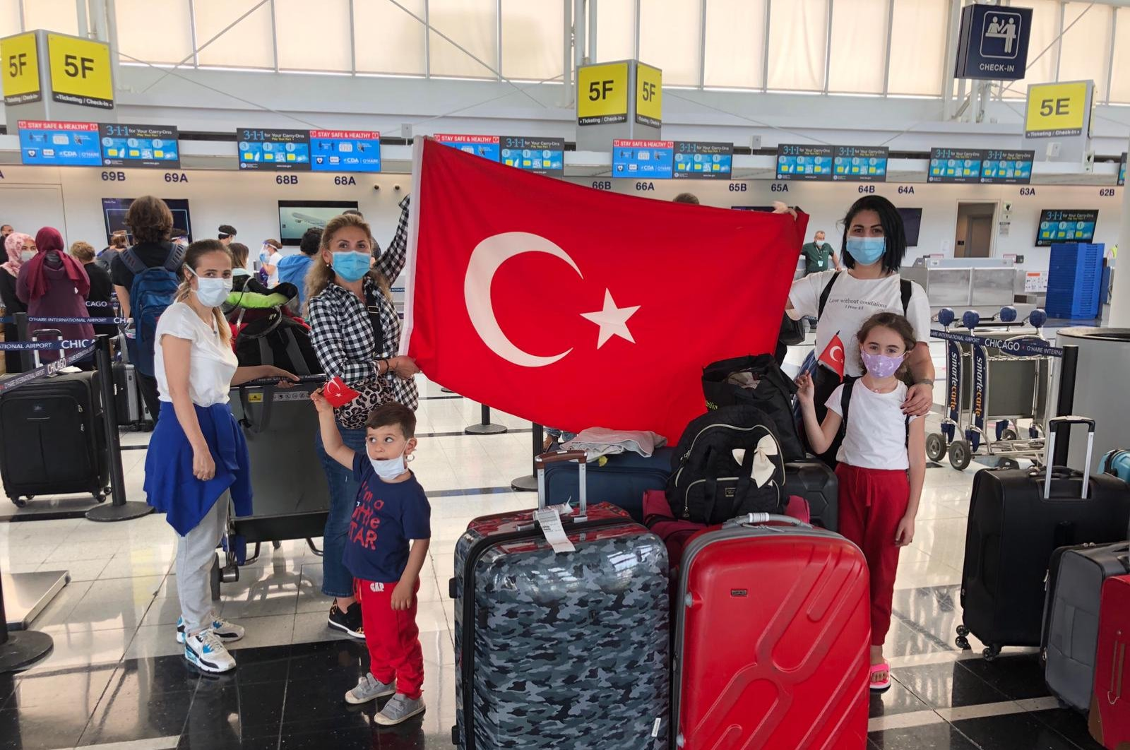 Evacuees hold a Turkish flag at O'Hare Airport before boarding their plane, Chicago, Illinois, U.S., June 3, 2020. (DHA Photo)