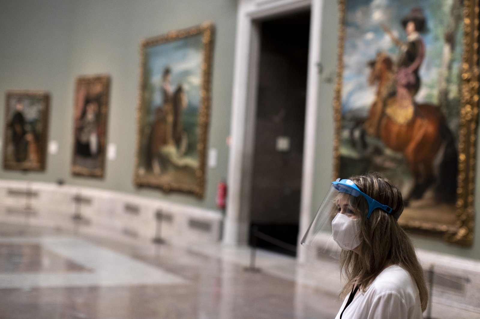 A staff member of museum wearing face mask and shield protection as protection against coronavirus stands for reopening on June 6 amid the coronavirus outbreak at Prado museum in Madrid, Spain, June 4, 2020. (AP)
