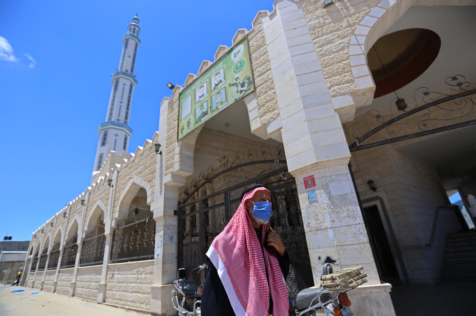 A Palestinian man wearing a mask stands right beside a mosque, Gaza, May 29, 2020.