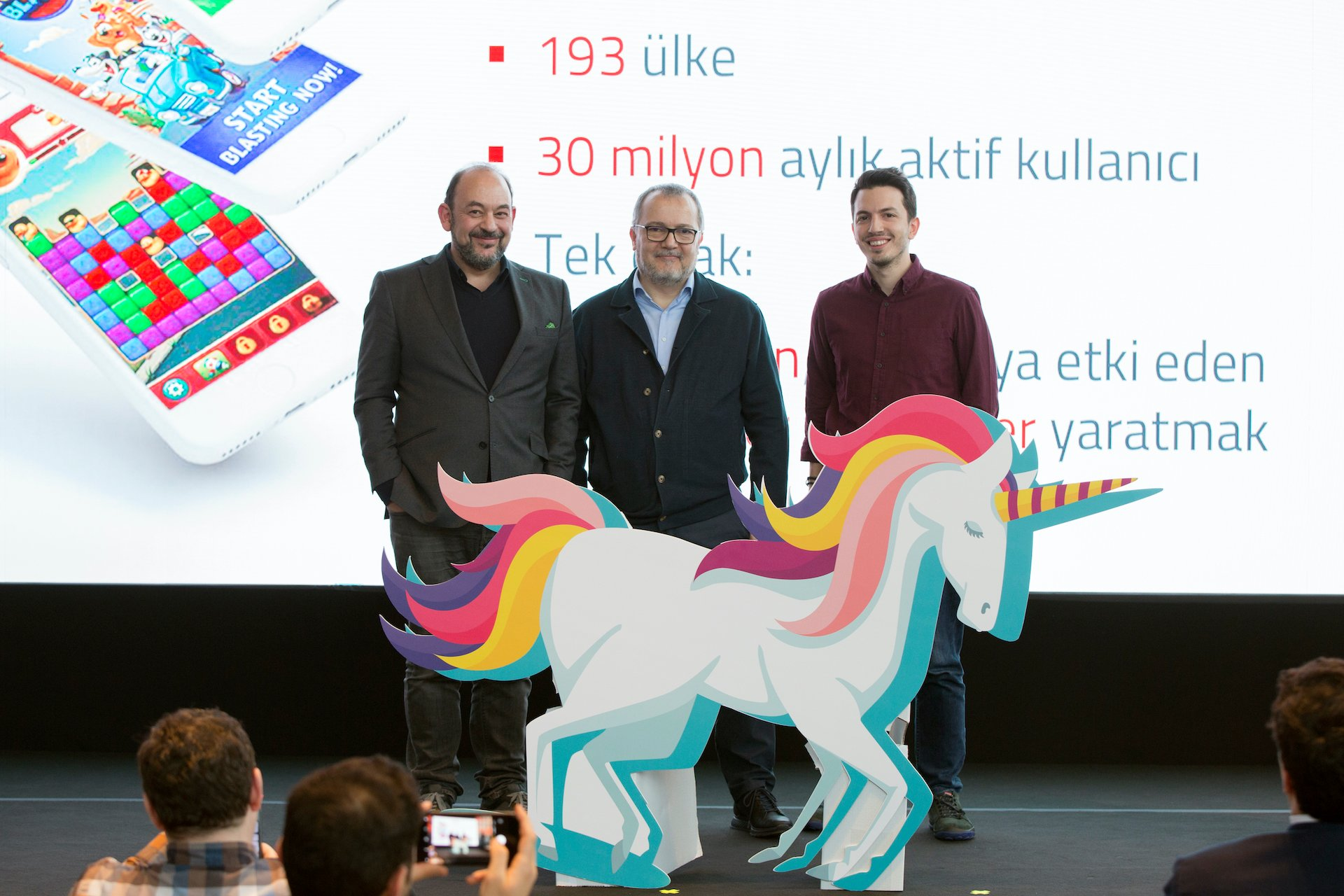 Sina Afra (L), the head of the Entrepreneurship Foundation and the founder of Evtiko, Peak Strategy Director Ömer İnönü (R) and Nazım Salur (C), the founder of Getir, pose in front of a unicorn during a startups.watch event in early 2020.