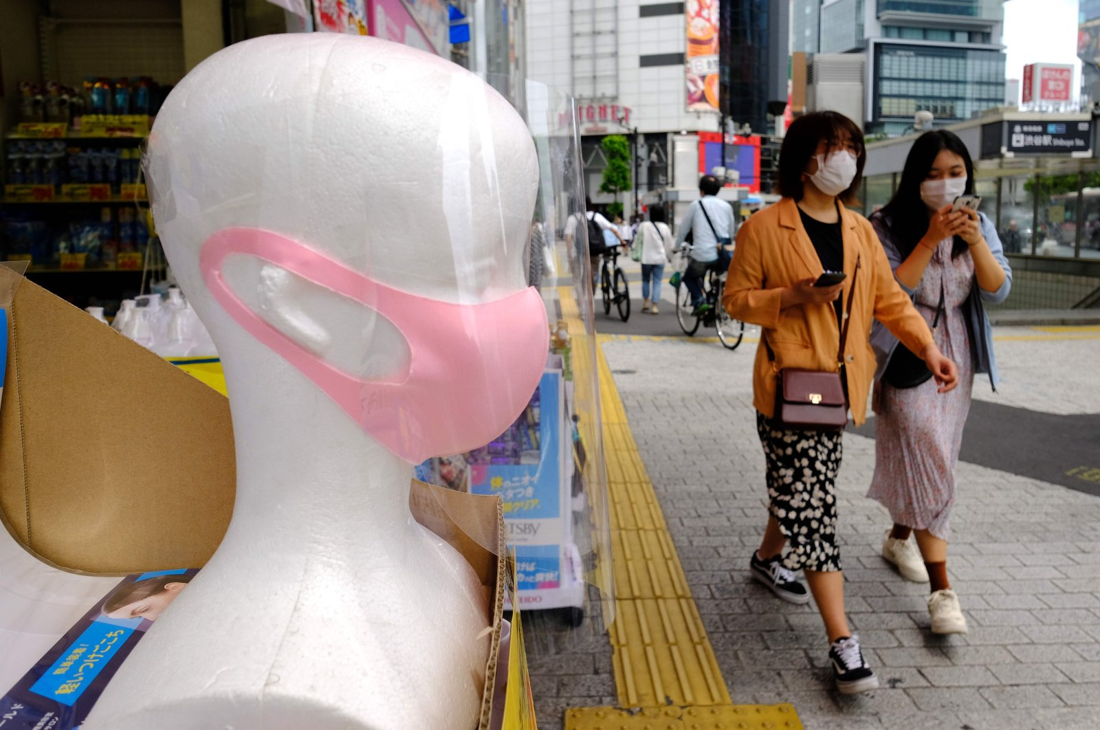 Pedestrians walk past a mannequin fitted with a face mask at a pharmacy in Tokyo, Japan, May 31, 2020. (AFP Photo)