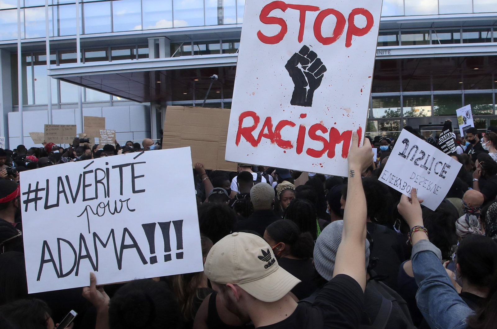 """People protest against racism outside the Palace of Justice, one with a poster reading """"Truth for Adama,"""" in Paris, France, June 2, 2020. (AP Photo)"""