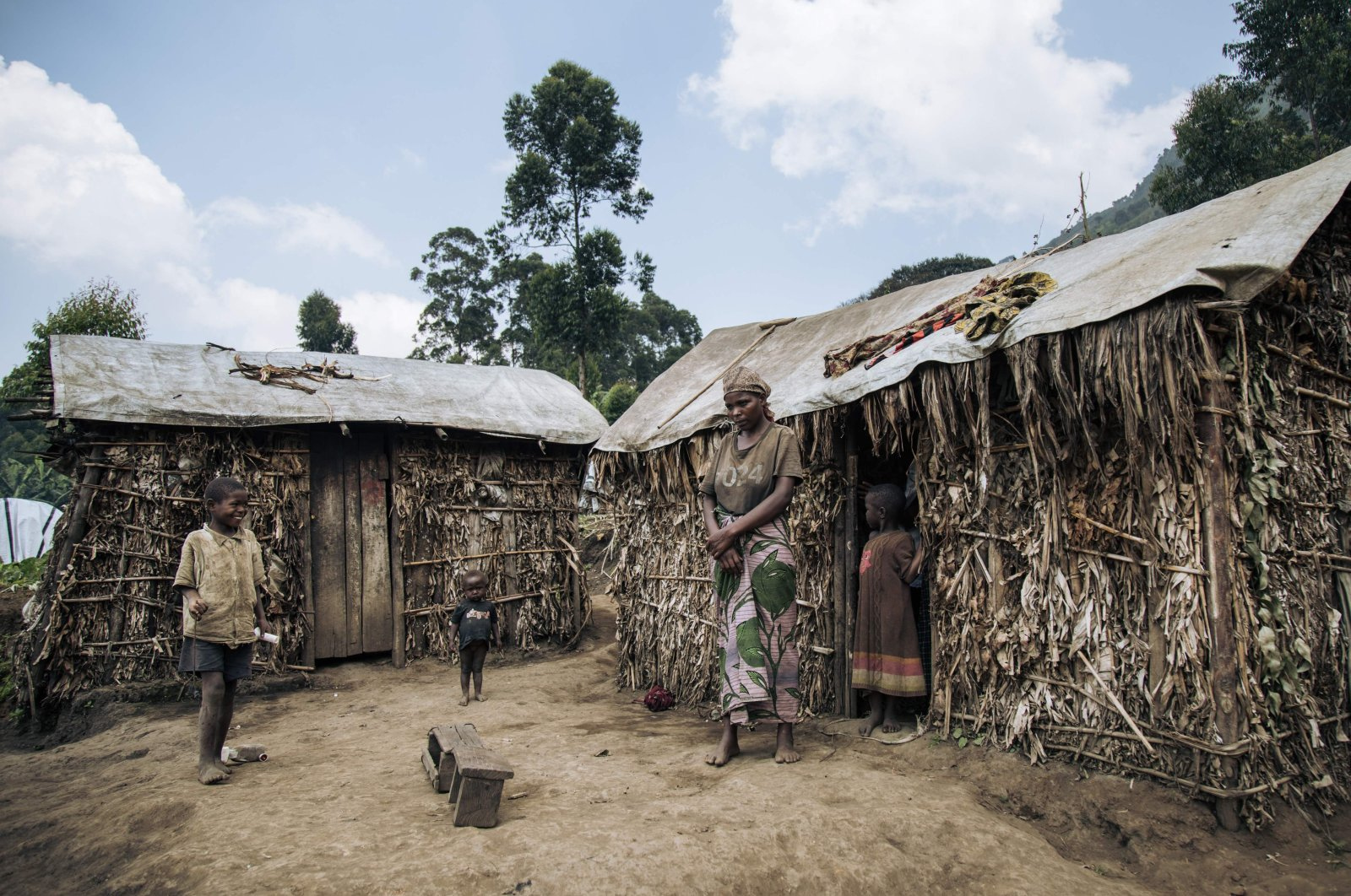 A woman stands next to a straw shelter with her children in Kalinga's site for internally displaced people in the Masisi Territory, the Democratic Republic of Congo, Jan. 15, 2020. (AFP Photo)